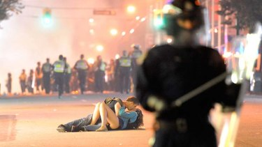 Stop for a kiss ...  this picture of Alexandra Thomas and Scott Jones cosying up while a riot went on around them in Vancouver went viral on the internet.