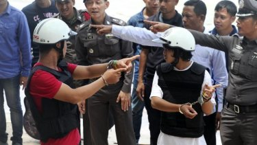 The two Myanmar men, in helmets and handcuffs, charged in the killings, were made to take part in a re-enactment of the crime.