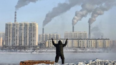 Big issue: A man exercises in the morning as he faces chimneys emitting smoke across the Songhua river in Jilin, northern China.