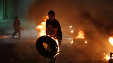 Burning issue ... a young demonstrator prepares to throw a tyre during a protest against the high cost of living near Ramallah.