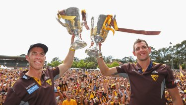 Coach Alastair Clarkson and captain Luke Hodge hold up the 2013 and 2014 premiership cups during the Hawthorn celebrations at Glenferrie Oval.