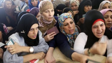 Suffocating closure: Palestinian women hoping to cross into Egypt present their passports at the Rafah border crossing in the southern Gaza Strip.