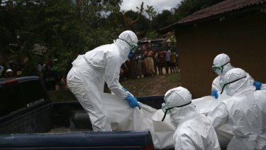 A burial team from the Liberian Red Cross carries the body of an Ebola victim from his home near Monrovia, Liberia.