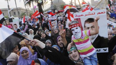 """Supporters of Egypt's ousted president Mohammed Morsi during a protest in Nahda Square on Tuesday, where protesters are camping. The posters reads: """"Yes for legitimacy, no for coup."""""""