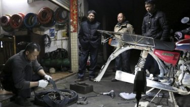 Lu Qiao and his  brothers watch as a roadside mechanic replaces a tyre on their motorcycle.
