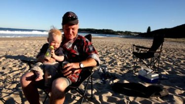 Splendid isolation... Reggie Weimer with his son Joe, 17 months, soaks up the peace of Catherine Hill Bay, which yesterday escaped a 600-home development.