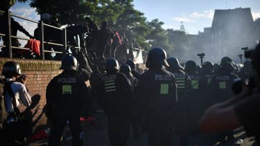 """HAMBURG, GERMANY - JULY 06: Protesters climb over a fence to escape riot police as they take part in the """"Welcome to Hell"""" protest march on July 6, 2017 in Hamburg, Germany. Leaders of the G20 group of nations are arriving in Hamburg today for the July 7-8 economic summit and authorities are bracing for large-scale and disruptive protest efforts tonight at the """"Welcome to Hell"""" anti-G20 protest. (Photo by Alexander Koerner/Getty Images)"""
