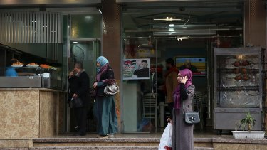 Palestinians buy from a shawarma restaurant with a poster of North Korean leader Jim Jong-un on the front window.
