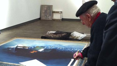 Signing off ... Charles Blackman signs one of the paintings in July 2011.