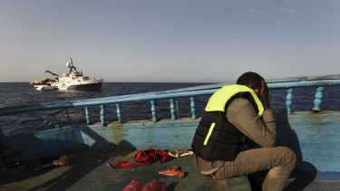 A refugee sits in despair on a wooden fishing boat as he waits to be rescued off the coast of Libya.