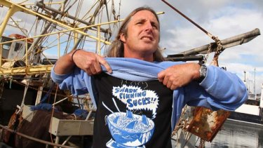 Tim Winton makes a stand in front of a gill-fishing boat at Fremantle's Fishing Boat Harbour. Winton is advocating that Australians be more selective on eating endangered shark species,.