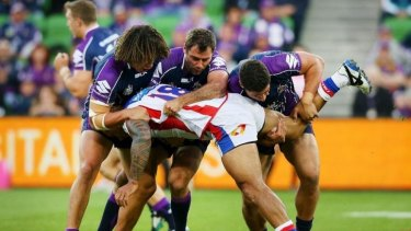 Three men in: David Fa'alogo is tackled by Kevin Proctor, Cameron Smith and Kenny Bromwich during the same match in which Knights teammate Alex McKinnon's career was ended.