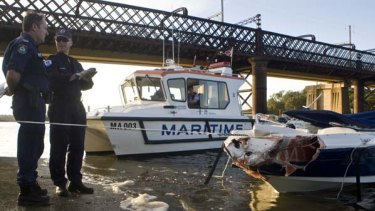 """""""The speedboat had heaps of people in it"""" ... officers inspect the damaged speedboat."""