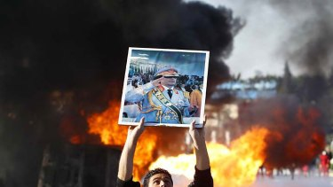 Burning desire for change ... a protester holds up a placard of Muammar Gaddafi in Tripoli.