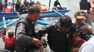 Rescuers assist a survivor of the sinking of an asylum seeker ship off West Java.