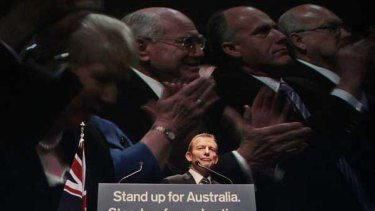 Tony Abbott launches the Coalition's campaign while images of the party faithful, including former prime minister John Howard, appear to be on the screen behind him. <i>Picture: Glen McCurtayne</i>