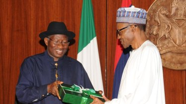 Goodluck Jonathan (left) presents a gift to Muhammadu Buhari at the presidential villa in Abuja, Nigeria.