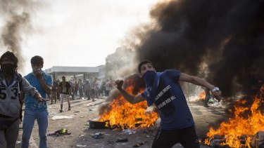 Horgos, Serbia. A protesting refugee throws projectiles at Hungarian police at the Horgos border crossing in Serbia.
