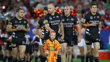 Greatest fan . . . The Wests Tigers run out at ANZ Stadium on Saturday night with five-year-old Lleyton Giles, who has a terminal liver disease.