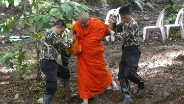 A Buddhist monk, helped by Thai rescues, walks after praying near the cave complex where the 12 boys and their soccer coach went missing.