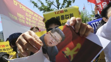 A North Korean defector tears a paper with a portrait of North Korean leader Kim Jong-un during a rally against the possible repatriation of North Korean restaurant workers to North Korea, in Seoul, last month.