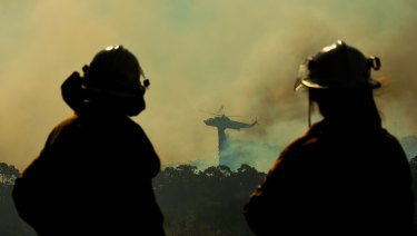 RFS crew members watch a helicopter dropping water on the fire front at Barden Ridge, Sydney.