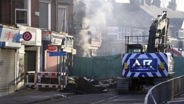 Emergency personnel continue to work at the scene of an explosion and fire Sunday night which destroyed a shop and building above in Leicester, England.