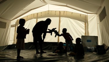 Children play with a carer in a makeshift childcare centre in PNG.