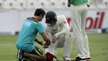 Australian captain Tim Paine receives treatment.
