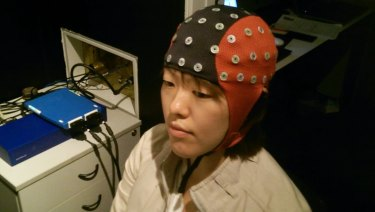 A woman wears an early stage epilepsy-predicting cap that's attached to a device.