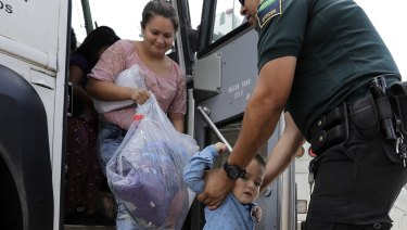 A transport officer helps immigrants Dilma Araceley Riveria Hernandez and her son, Anderson Alvarado, 2, get off the bus after they were processed and released by US Customs and Border Protection in McAllen, Texas.