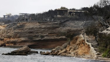 Firefighters stand on a cliff top where burned trees hug the coastline in Mati east of Athens, Tuesday.