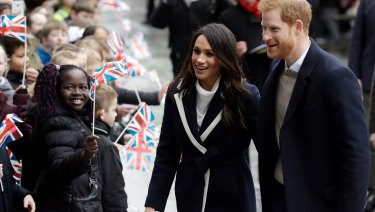 Prince Harry and his fiancee Meghan Markle are greeted by flag-waving school children in Birmingham.