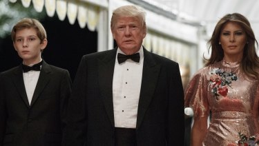 President Donald Trump arrives for a New Year's Eve gala at his Mar-a-Lago resort with first lady Melania Trump and their son Barron in Palm Beach, Florida.