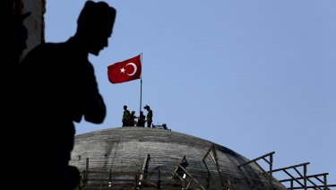A sculpture of Turkey's founder Kemal Attaturk, sits on the monument of the Republic, as construction workers beyond place a Turkish national flag on the dome of the under-construction mosque in Taksim square in Istanbul.