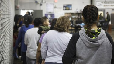 Teens who have been taken into custody related to cases of illegal entry into the United States, stand in line at a facility in McAllen, Texas.