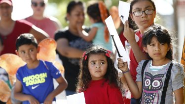 Children listen to speakers during an immigration family separation protest in Phoenix, Arizona, on Monday.