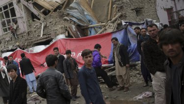 Residents walk through the site of the suicide attack in Kabul, Afghanistan, on Friday.