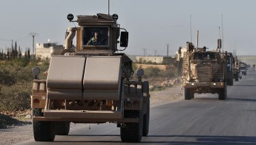 A US mine detector armored vehicle leads a convoy of US troops on a road leading to the tense front line with Turkish-backed fighters in Manbij town, Syria.