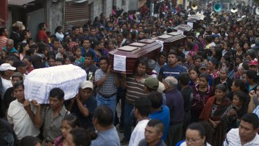 People carry the coffins of seven victims to the cemetery in San Juan Alotenango, Guatemala, on Monday.