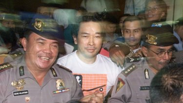 A police officer, left, smiles as he escorts Tommy, fugitive son of former Indonesian President Suharto, through a mob of reporters after his capture at police headquarters in Jakarta, Indonesia.