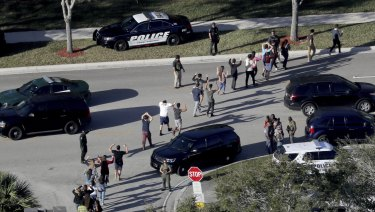 Students hold their hands in the air as they are evacuated by police from Marjory Stoneman Douglas High School.