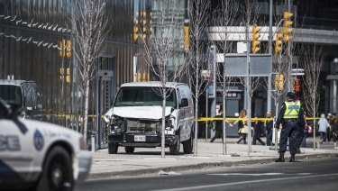 Toronto police officers stand near a damaged van after it  mounted a sidewalk crashing into pedestrians in Toronto.
