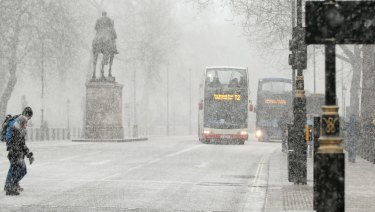 Pedestrians cross Whitehall as snow falls in London on Tuesday.