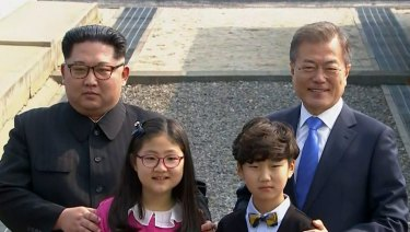 North Korean leader Kim Jong-un, left, and South Korean President Moon Jae-in, right, pose with children as Kim crossed the border into South Korea for their historic face-to-face talks.