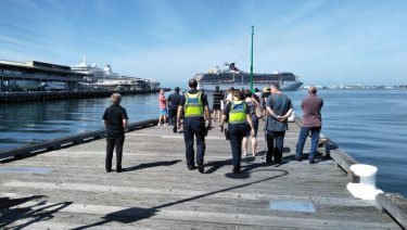 Onlookers and police waiting for the arrival of the Carnival Legend cruise ship at Melbourne's Station Pier  on Saturday.