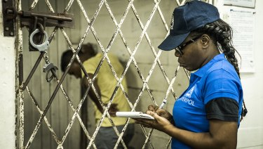 An Interpol officer writing documents during a raid in night clubs in Georgetown, Guyana.