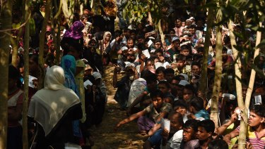 Rohingya refugees sit in a queue at a Red Cross distribution point in Cox's Bazar, Bangladesh.