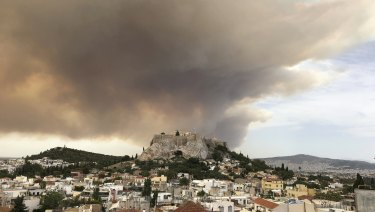 A pall of smoke turns large parts of the sky orange, with the ancient Acropolis hill at centre.