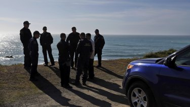 California Highway Patrol officers and deputy sheriffs gather after a search for three missing children at the site where the bodies of Jennifer and Sarah Hart and three of their adopted children were recovered two days earlier.